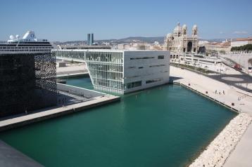 Sèten uutta vau-arkkitehtuuria. Musta museokuutio Mucem ja kongressikeskus. Taustalla renessanssiaan elevä Marseillen katedraali.